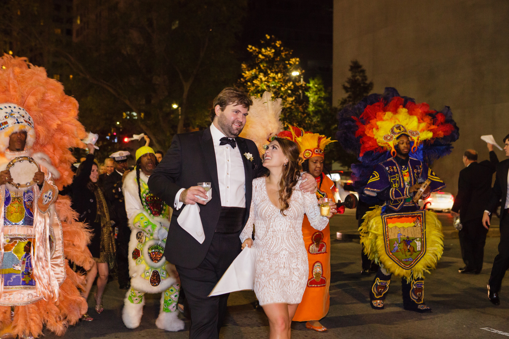bride in short dress with groom walking in the street with mardi gras indian second line parade
