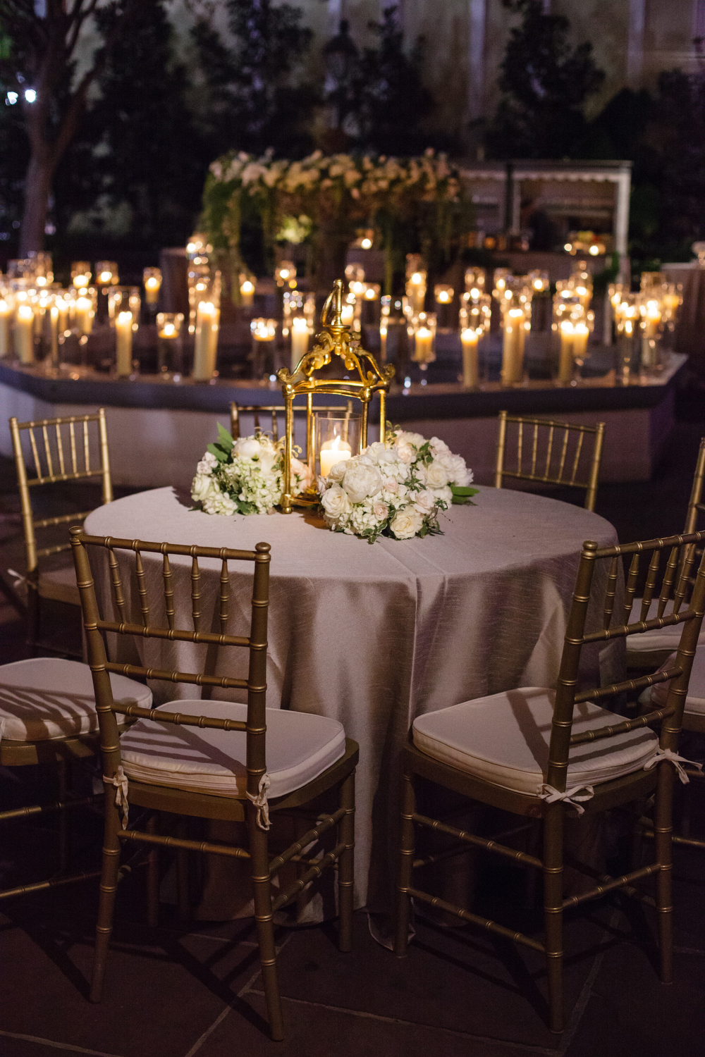 small wedding reception table with golden lantern and candle light around a fountain in an outdoor courtyard at night