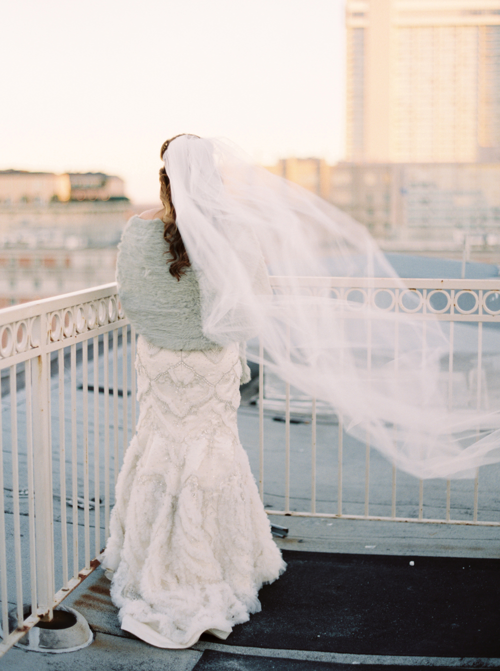 back of bride in gown wearing fur stole with long white veil flowing behind her as she looks at the city skyline