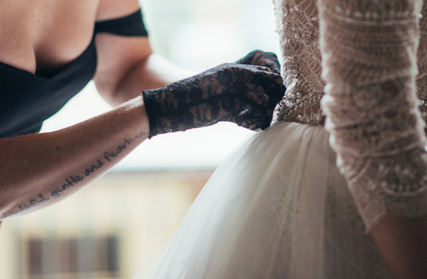 bride getting zipped in to her dress by her mom wearing black lace gloves
