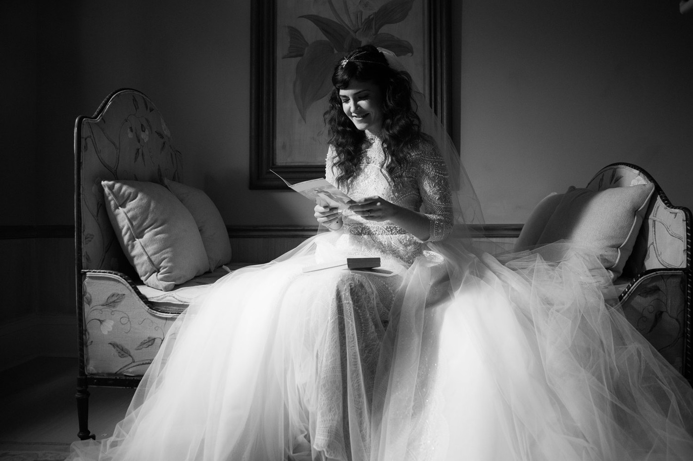 Bride sitting on a chair in her long white gown reading a letter and smiling