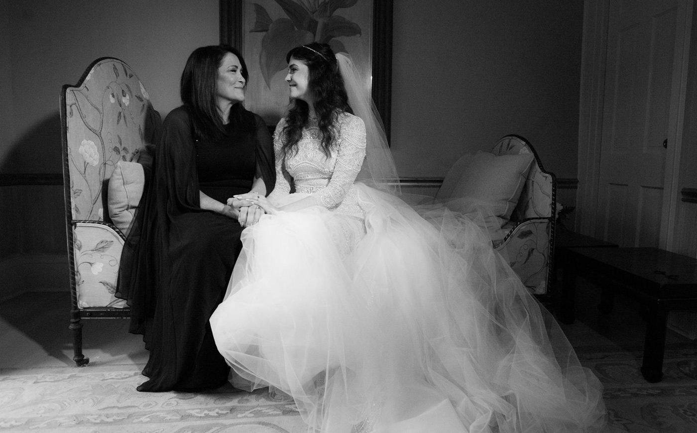 Bride and her mother holding hands in her bridal suite