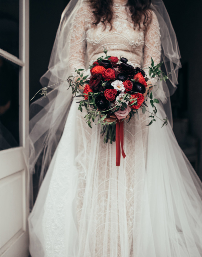 Up close of the Brides detailed gown and her black, red and white bouquet with red velvet ribbon hanging