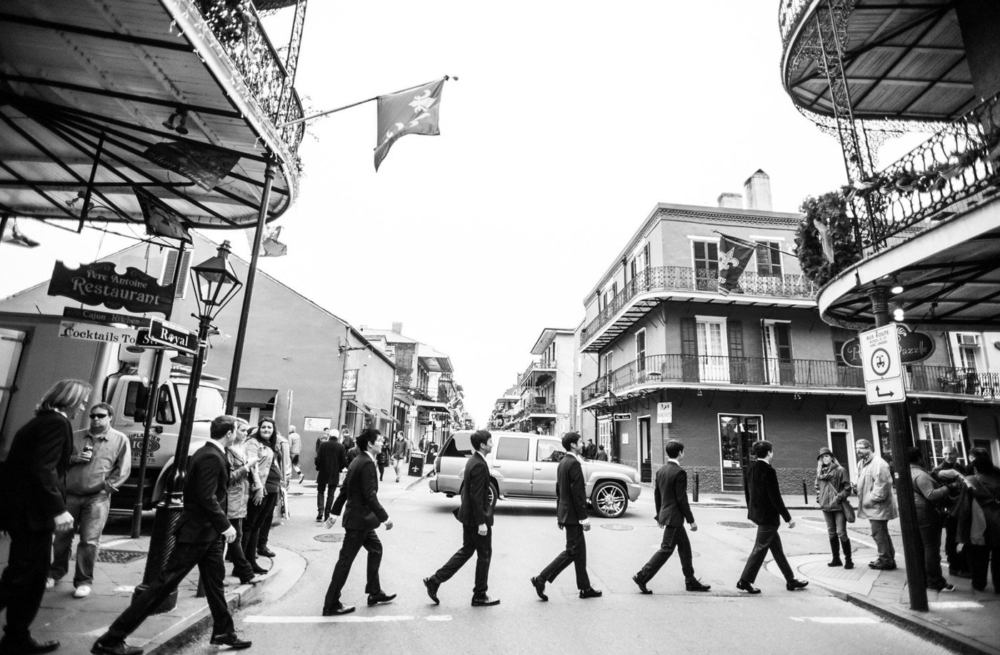 black and white photo of groomsmen walking across a street in the French Quarter