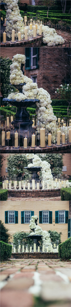 white hydrangeas cascading down the fountain with candles around the fountain