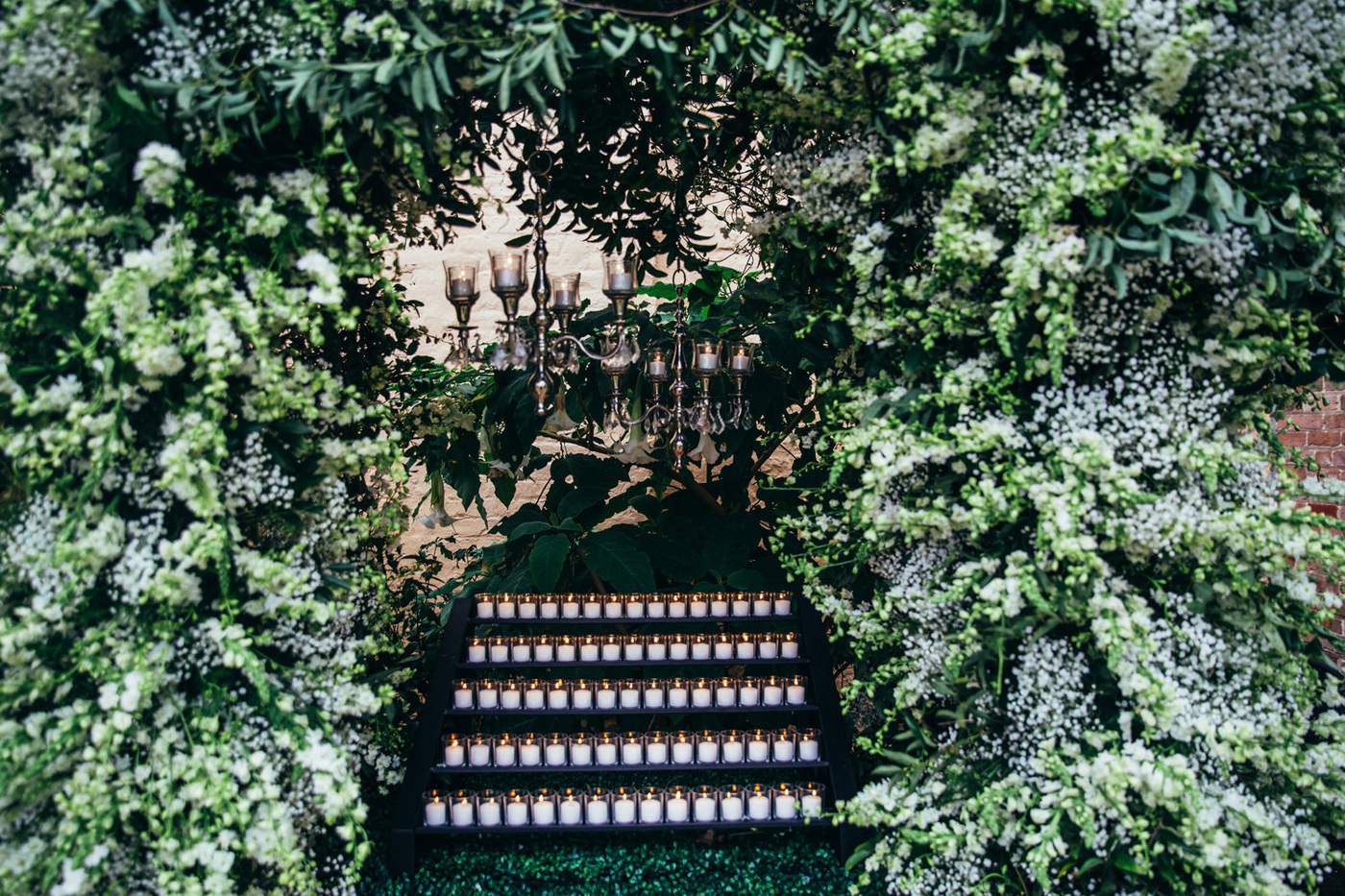 Close up photo of votive candles lit inside of cascading greenery