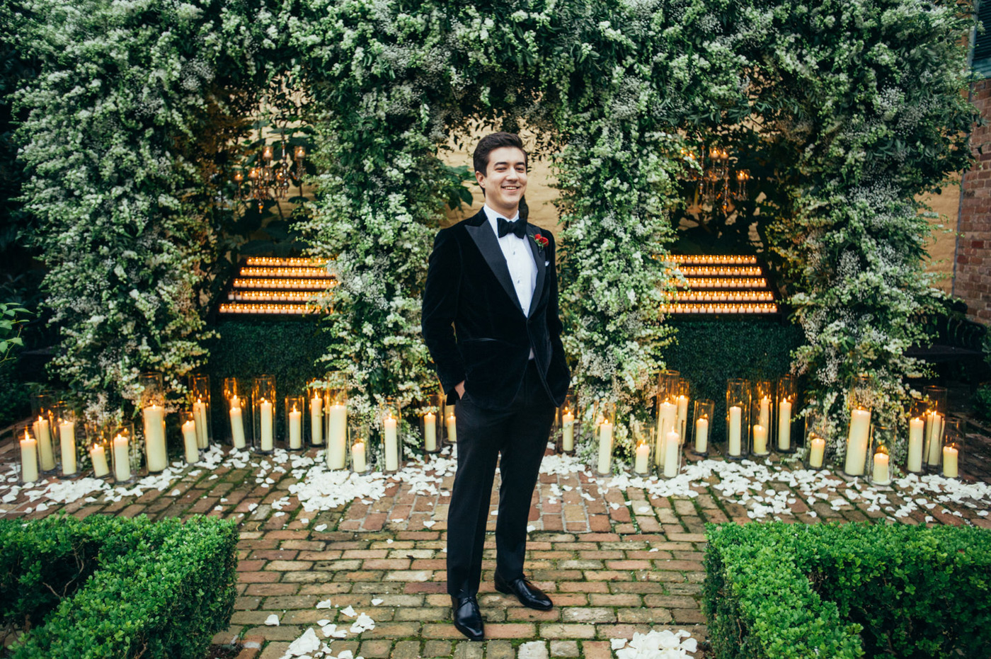 Groom smiling in his black velvet tux with a red boutonniere in front of candles and greenery
