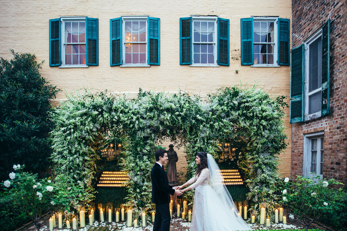 Bride and groom hold hands in front of greenery draping behind them and candles flickering with white rose petals on the ground