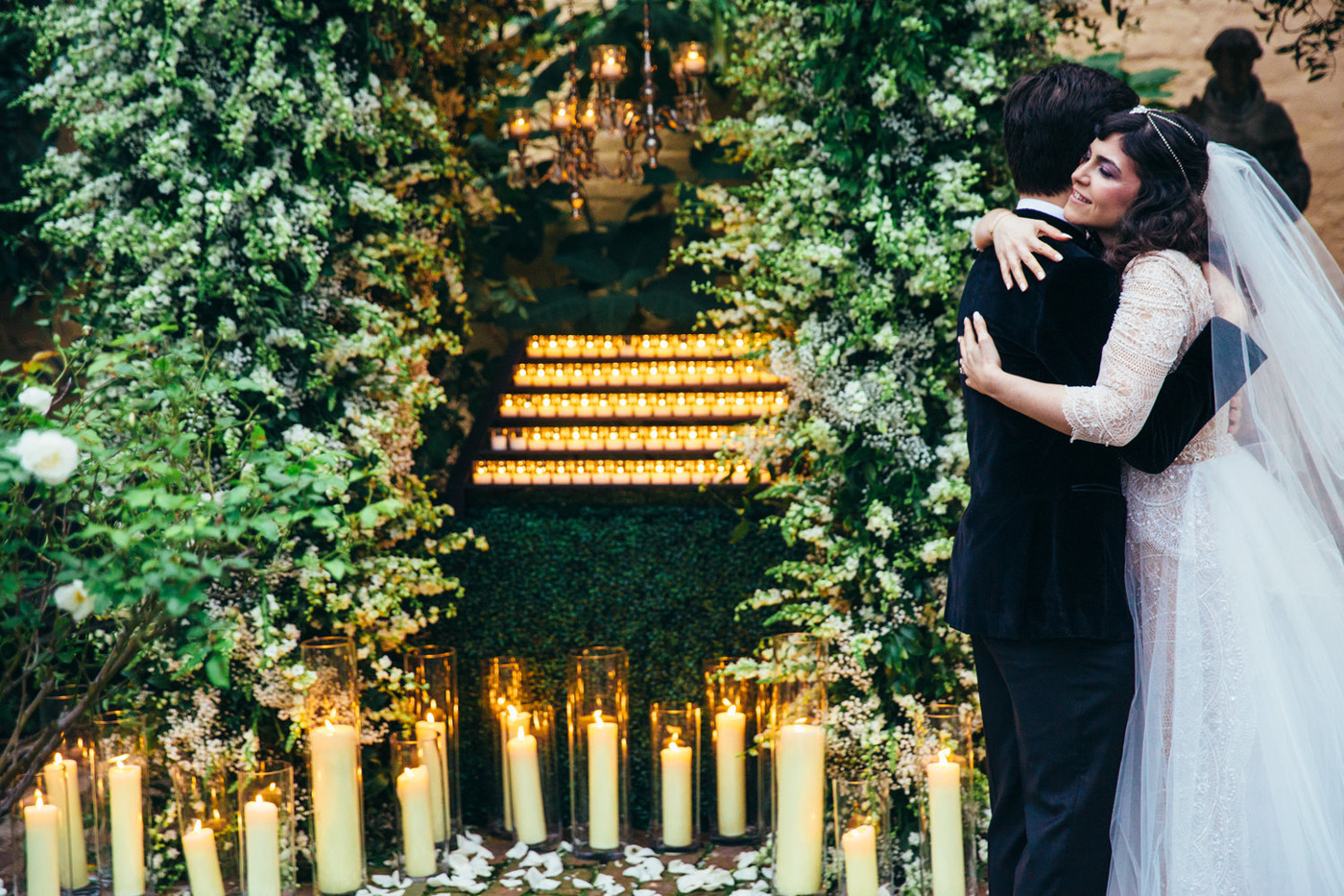 Bride and groom hugging in front of a candle lighting space in the middle of greenery with white rose petals