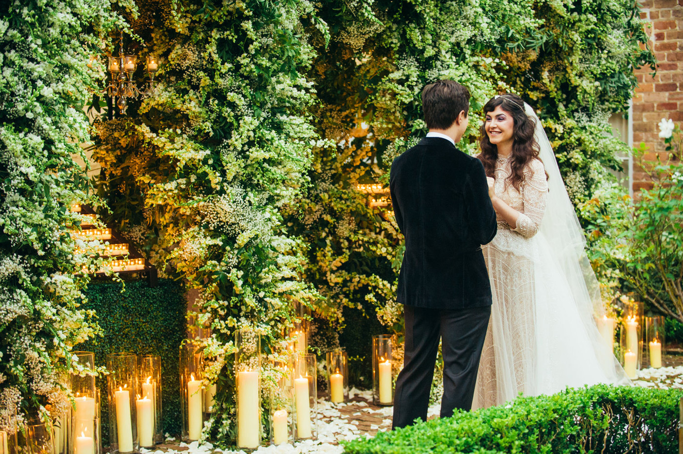 Bride and groom facing each other smiling in front of a luscious greenery back drop and candles on the ground in clear vases