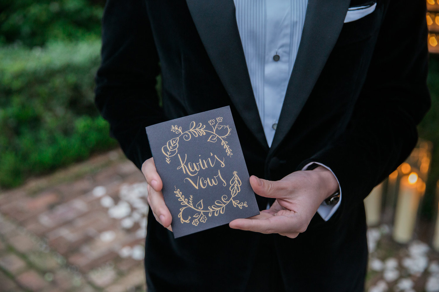 Groom holding his black and gold vow book while wearing a black velvet suit
