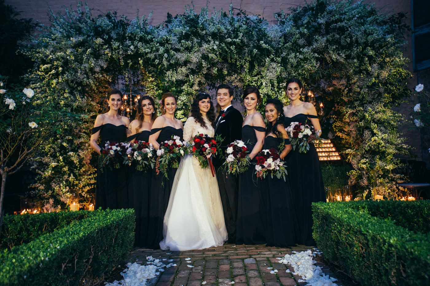 Bride standing next to her bridesmaids in their black bridesmaid dresses with green, red and white bouquets in front of a lush green and white floral backdrop