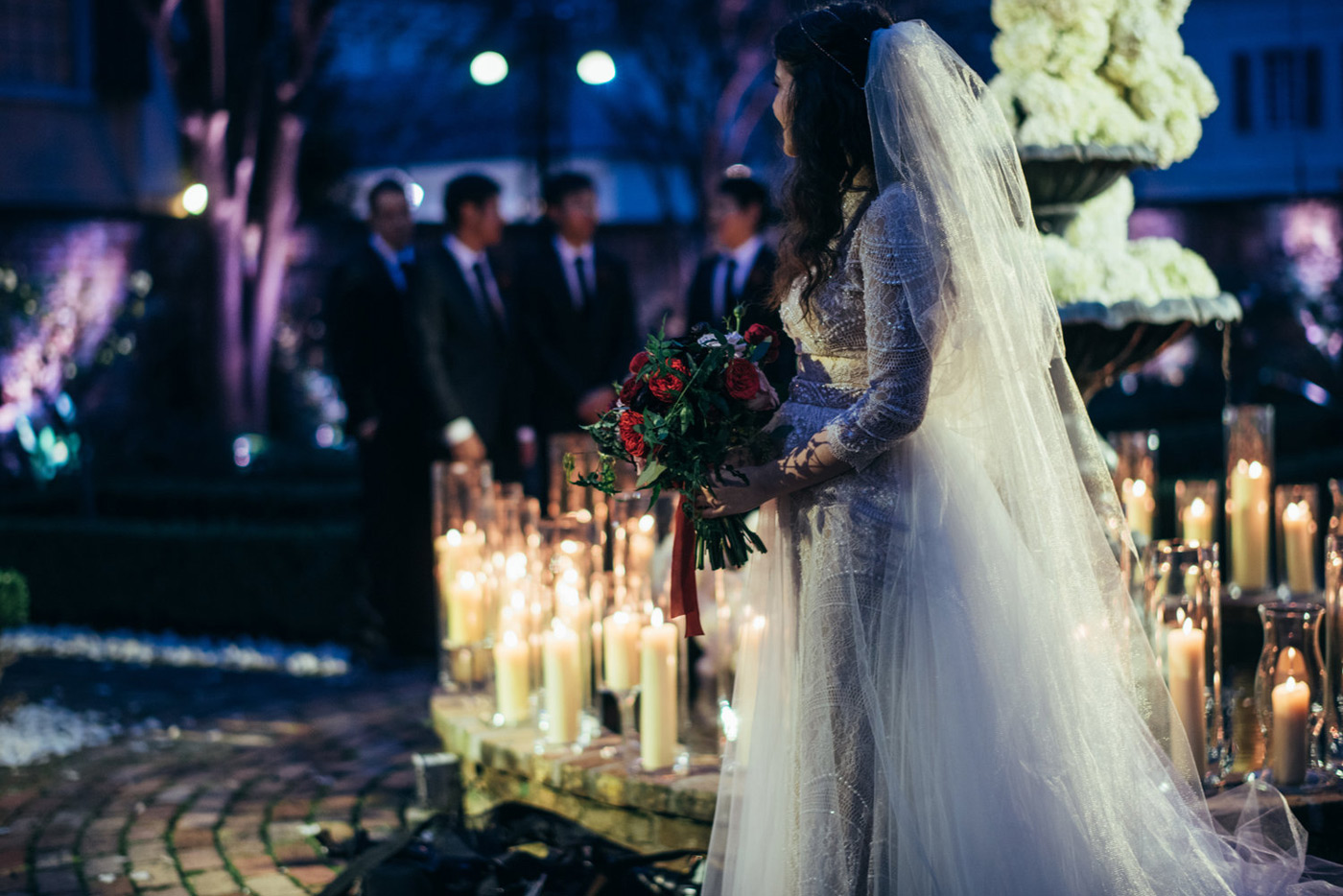 Bride walking down the isle next to flickering candles circling the outside fountain filled with white  hydrangeas