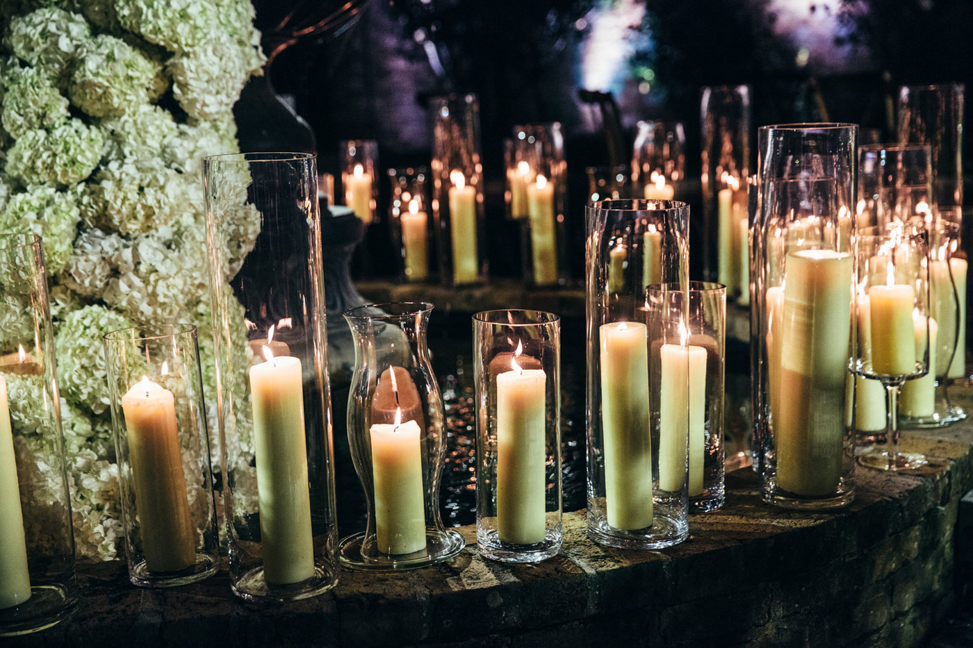 Candles in tall glass vases layered around a fountain in the night
