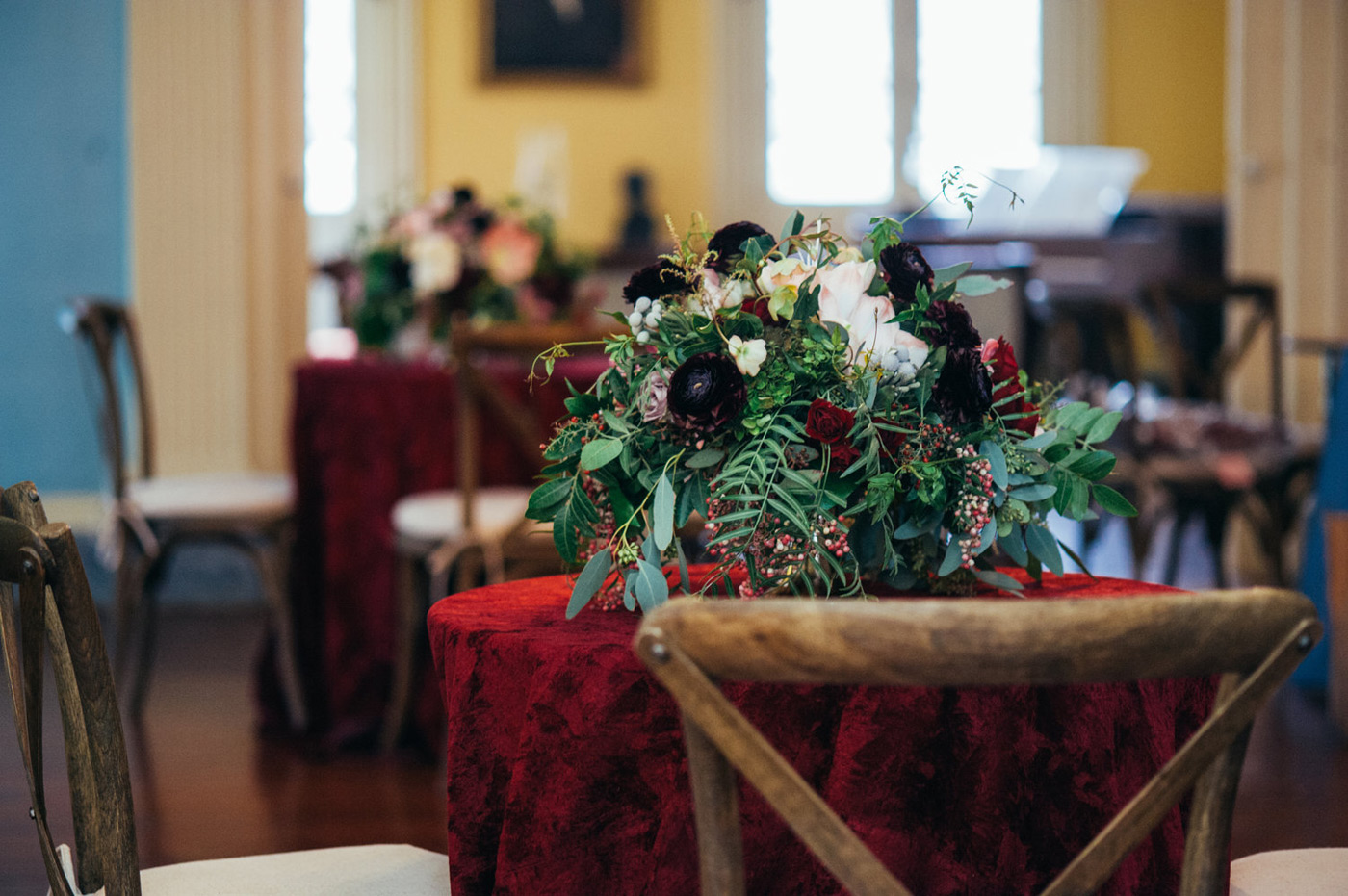 Gorgeous floral arrangement of deep red and white flowers and luscious greenery on top of a dark red velvet table cloth