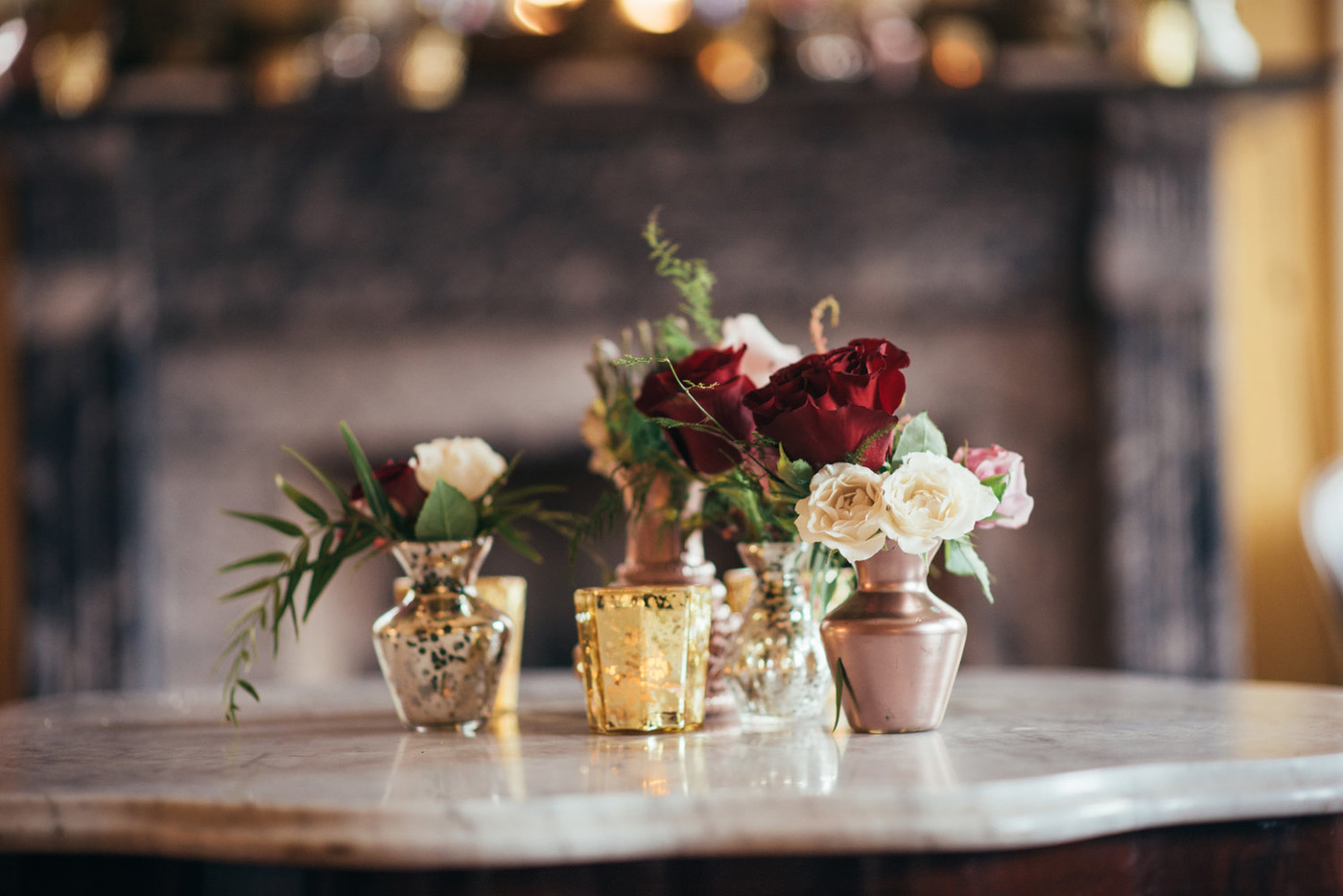 red and white roses inside of small vases and tea lights