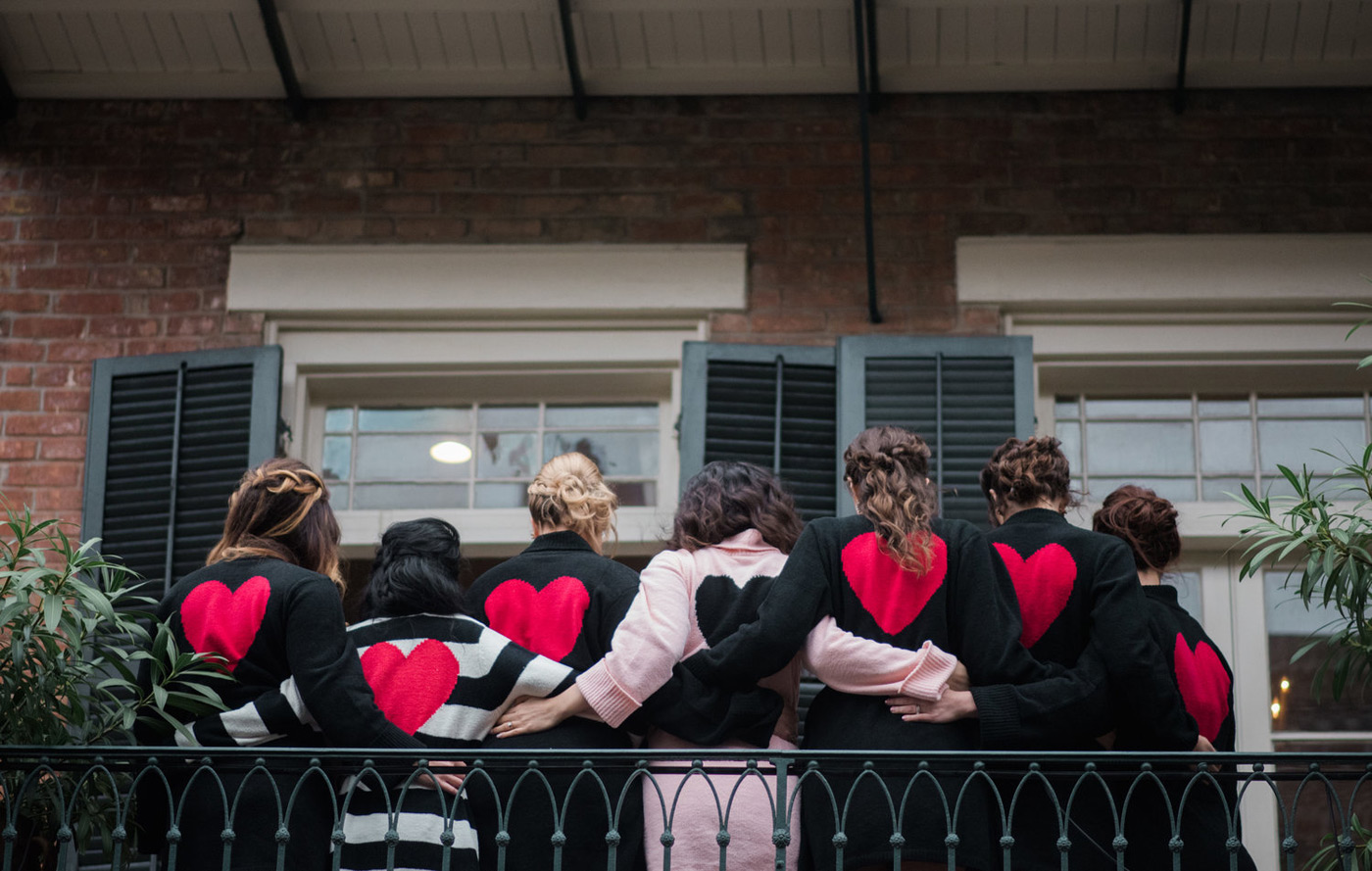 Bride and Bridesmaids on a balcony holding each other with red hearts on the back of their robes