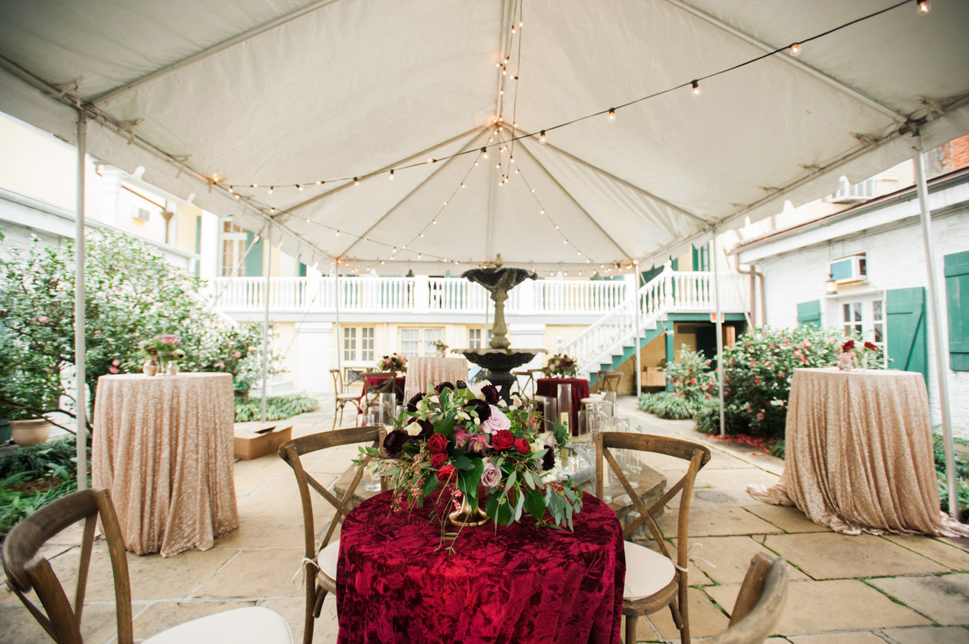 Wedding reception seating with red velvet table cloths, beautiful floral arrangements and string lights hanging from a white tent