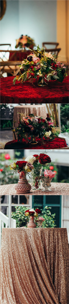 Luscious red and green floral arrangements sitting on red velvet and gold table cloths