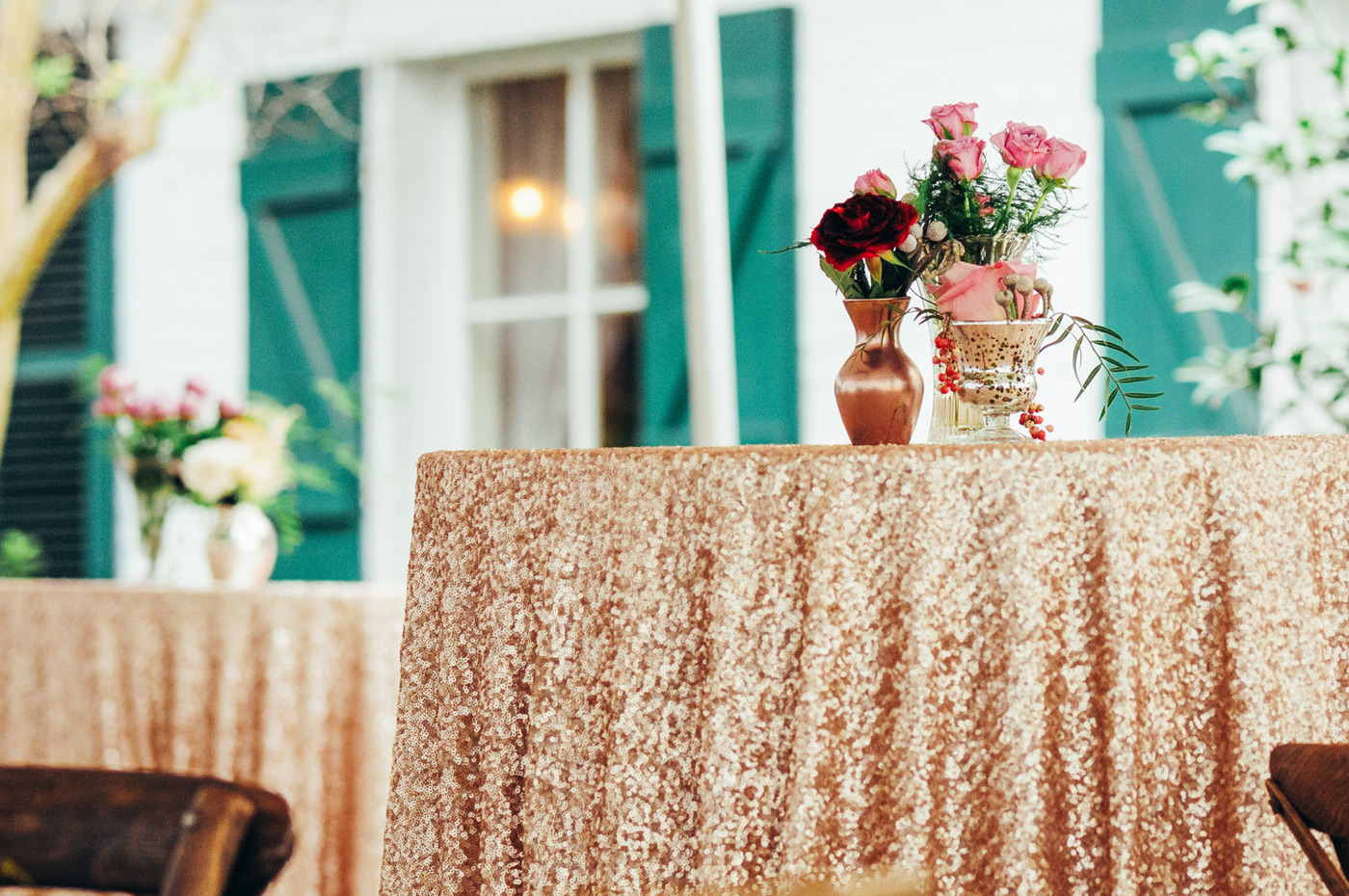 Pink and red roses sitting on top of a gold sparkly table cloth over a high boy table