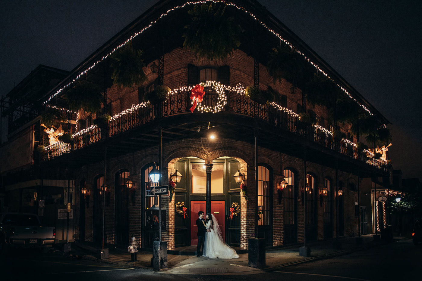 Bride and Groom pose in from of a traditional New Orleans building with Christmas lights around the balcony