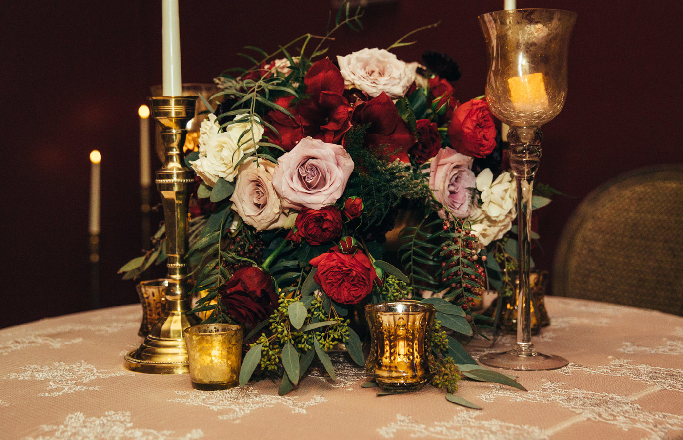 Floral arrangement with red, pink, and white roses and lush greenery on a blush table cloth with brass candlesticks