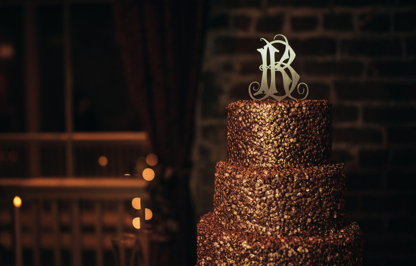 Shiny bright gold tiered wedding cake with a monogram on top