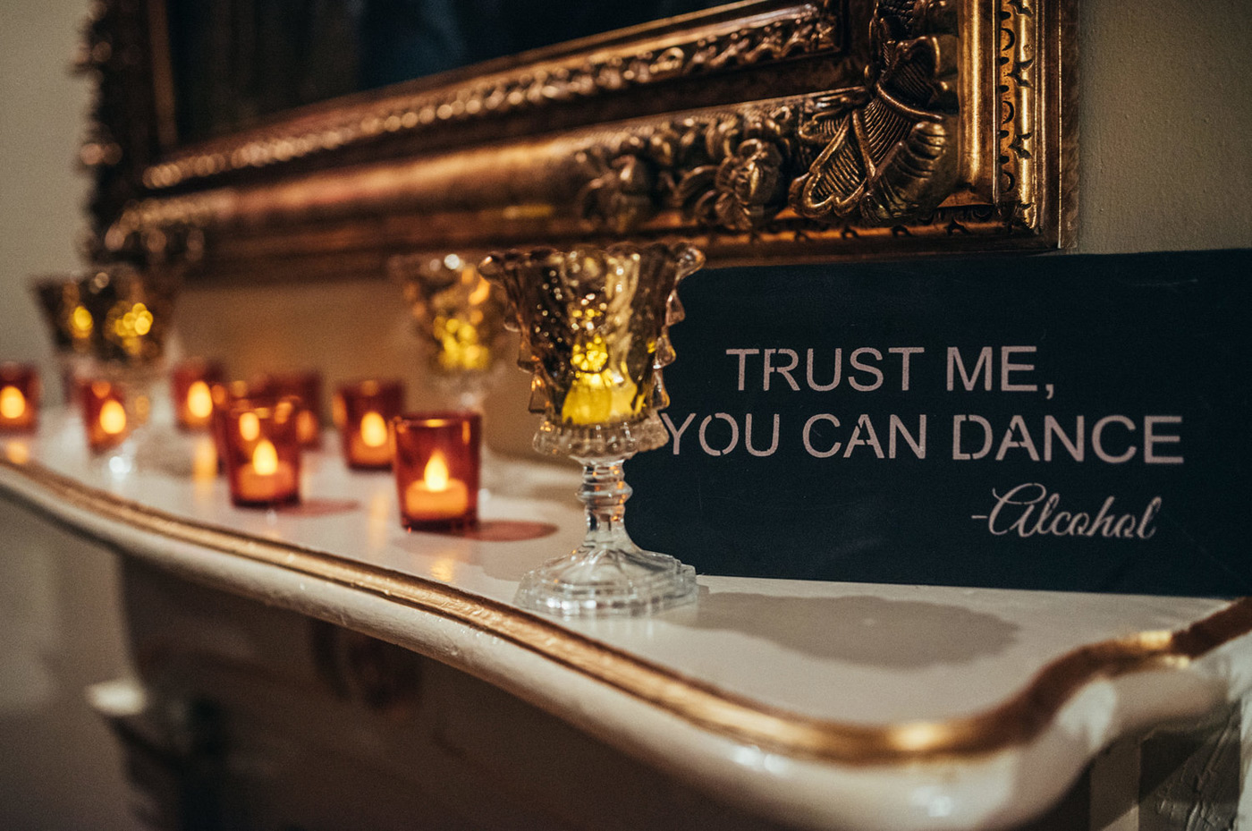 """Trust me you can dance, Alcohol"" sign next to tea lights and a gold mirror"