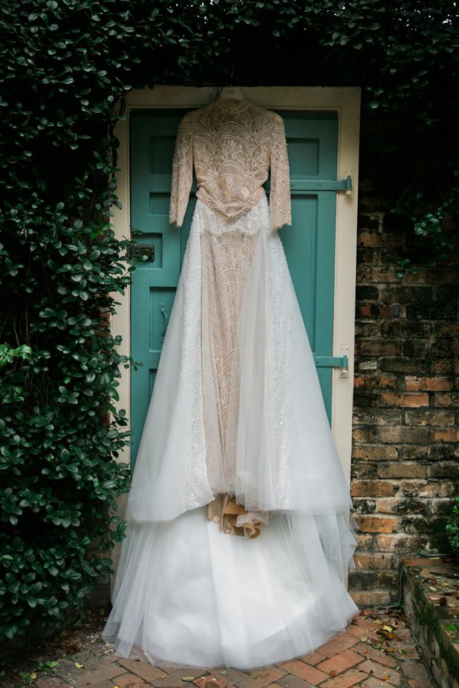 Wedding gown handing over a turquoise door with greenery around