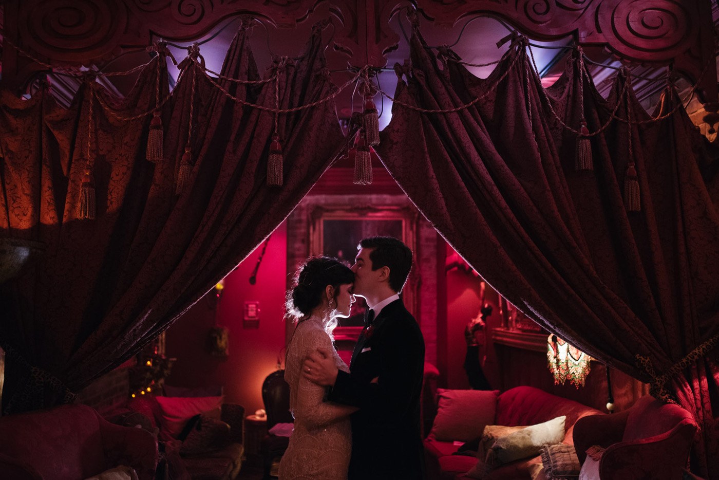Groom kissing bride in dark red lit room with lush curtains above