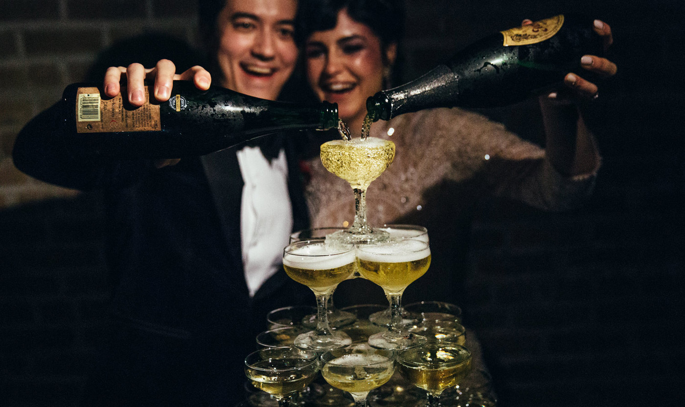 Bride and groom pouring bottles of champagne over their bubbling champagne tower