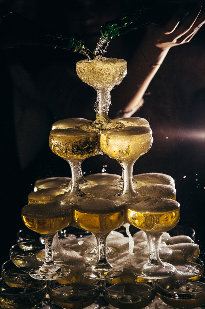 up close photo of a bubbly champagne tower flowing down the glasses