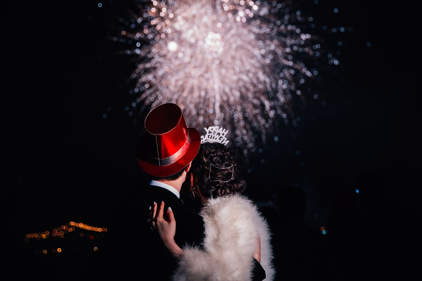bride and groom in New Years Eve hats looking at bright fireworks in the sky