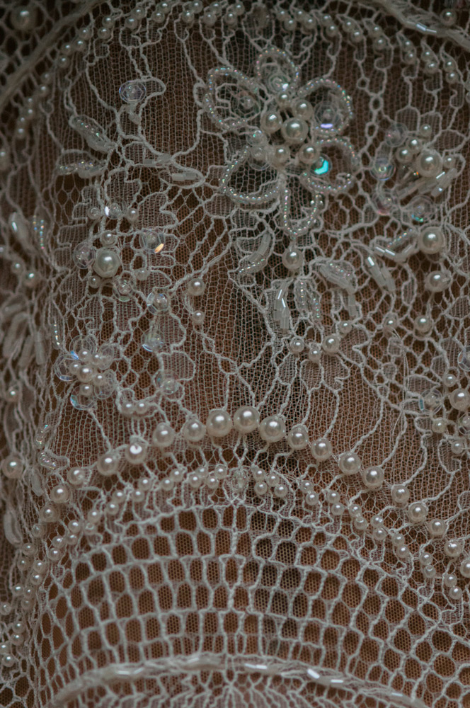 close up photo of the brides beaded gown with pearls and sequins