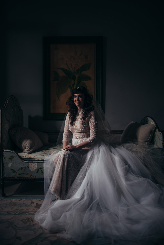 Portrait of the bride sitting with her long tulle dress cascading down to the floor and the beautiful beading on the top of her dress