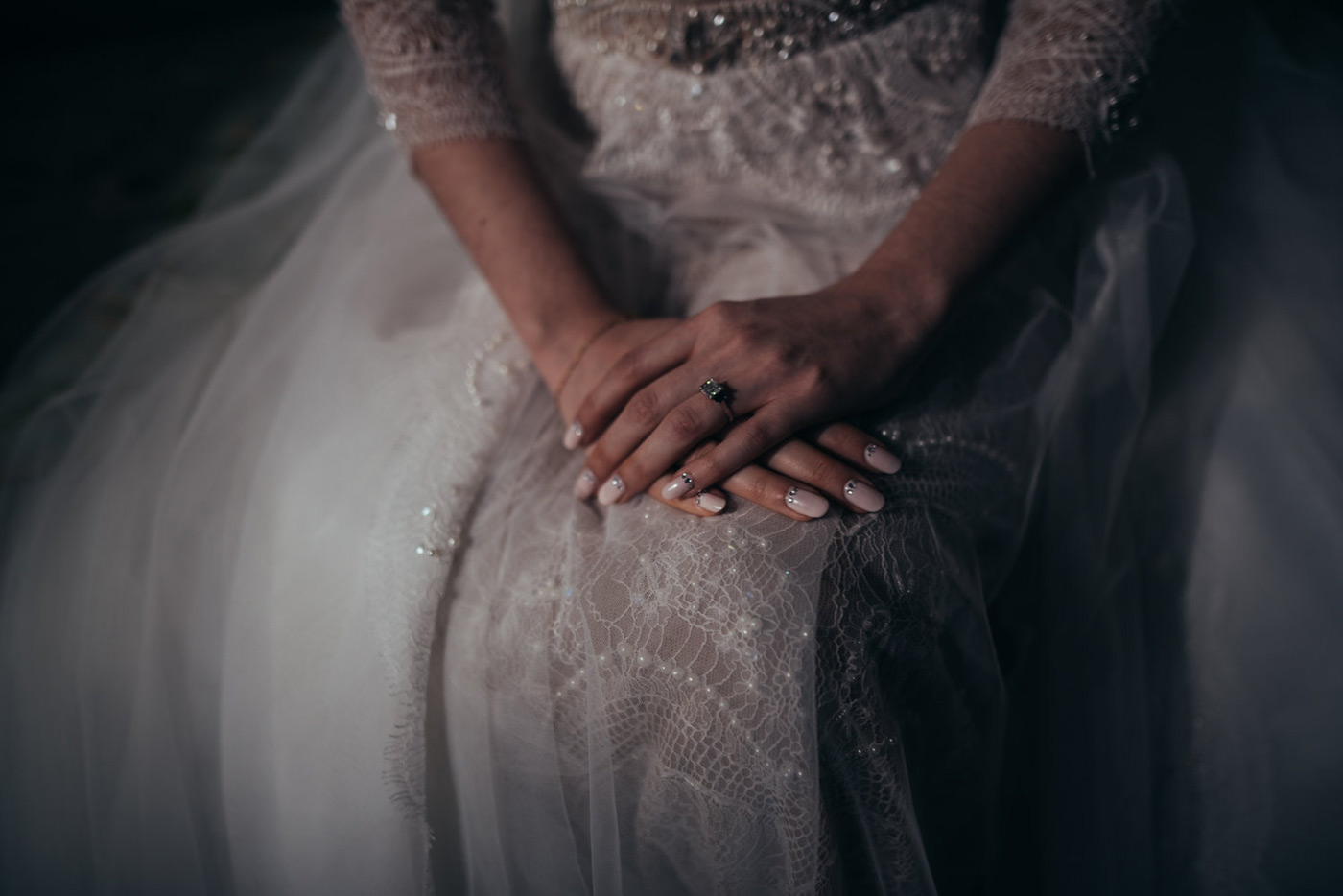 close up photo of the brides gown with pearl beading and her light pink nails