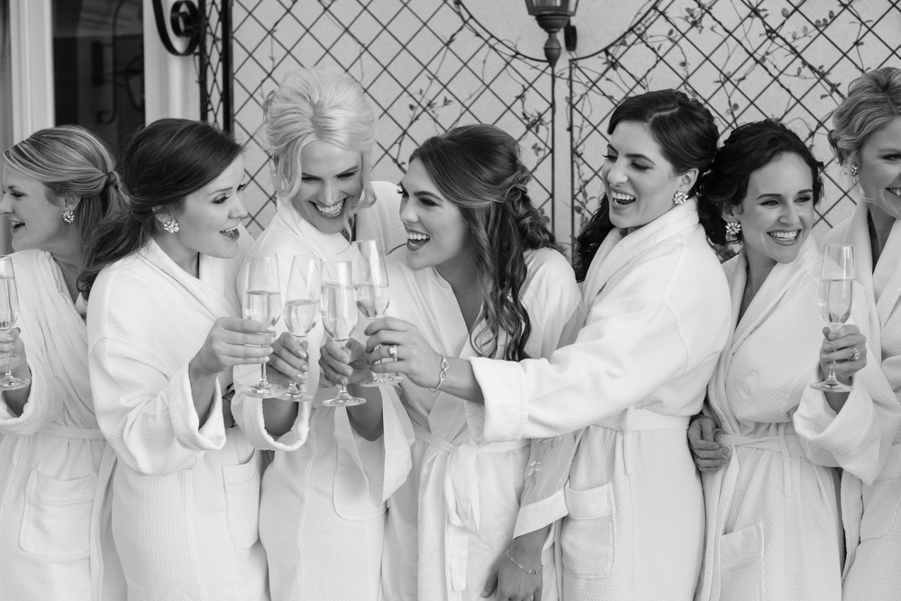 bride with bridesmaids in robes toasting champagne and smiling