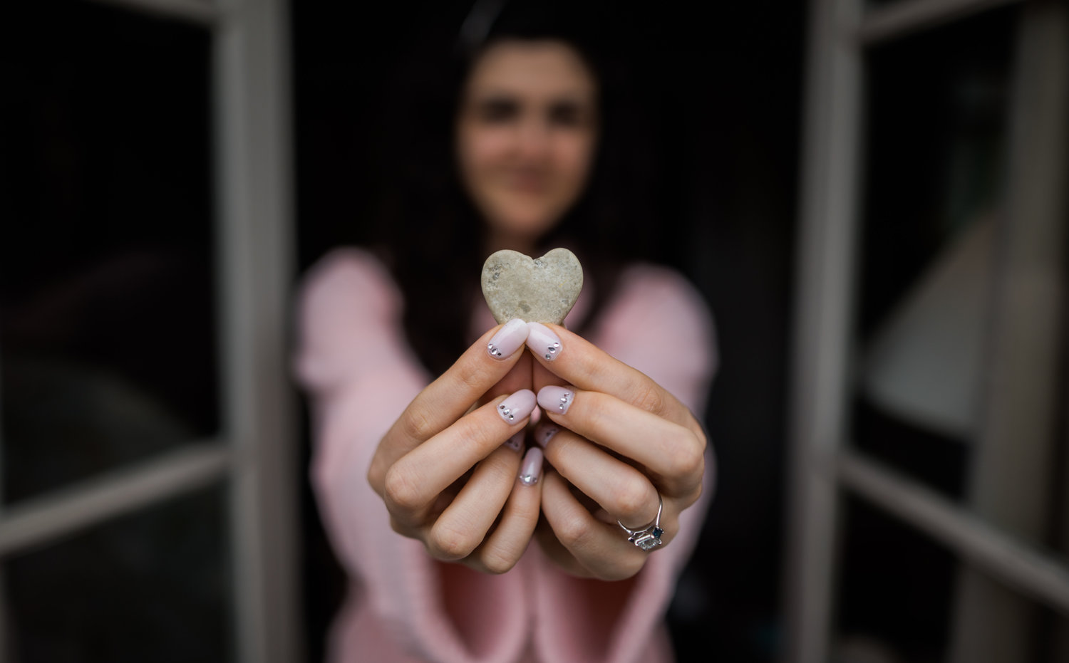 bride holding a heart rock with pink nails and pink robe