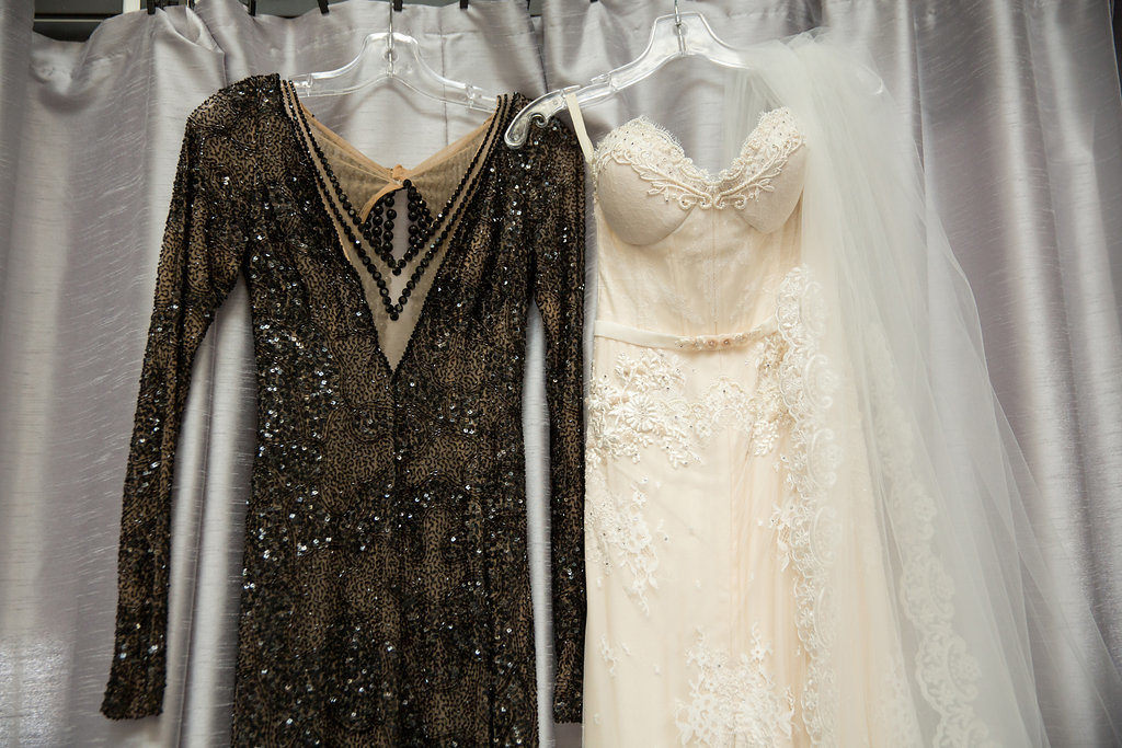 white bridal gown and veil hanging next to black beaded reception gown for wedding