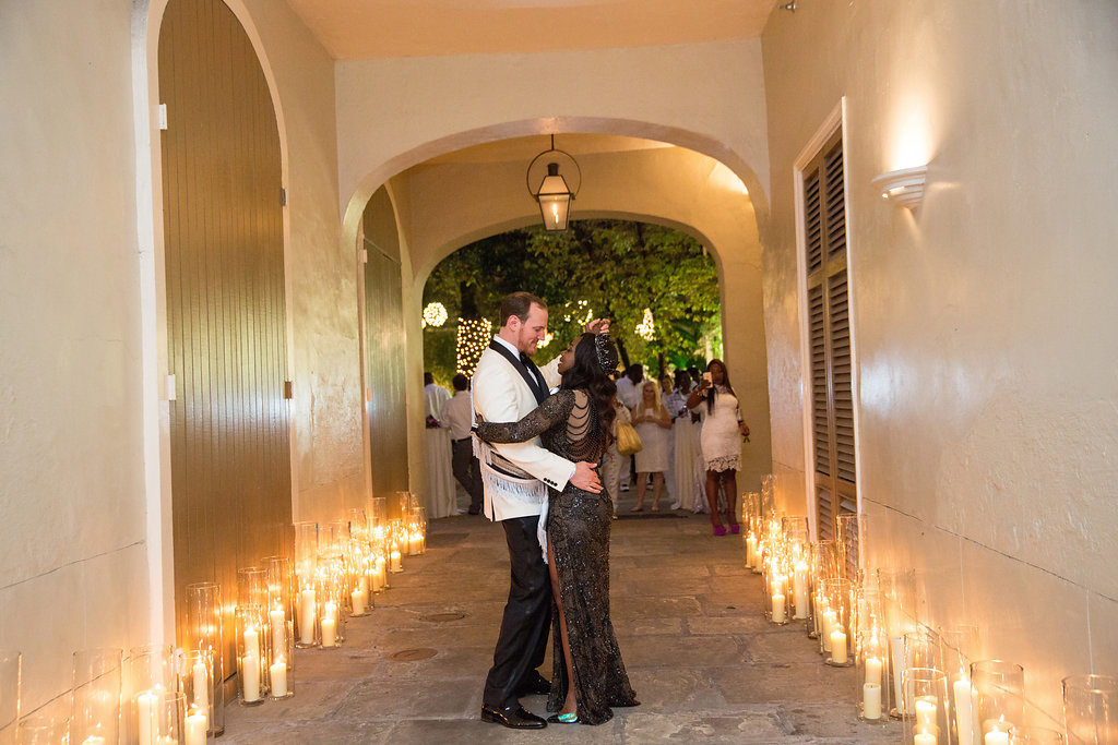 bride adn groom embracing in the carriageway of a French Quarter courtyard with candle light surrounding them