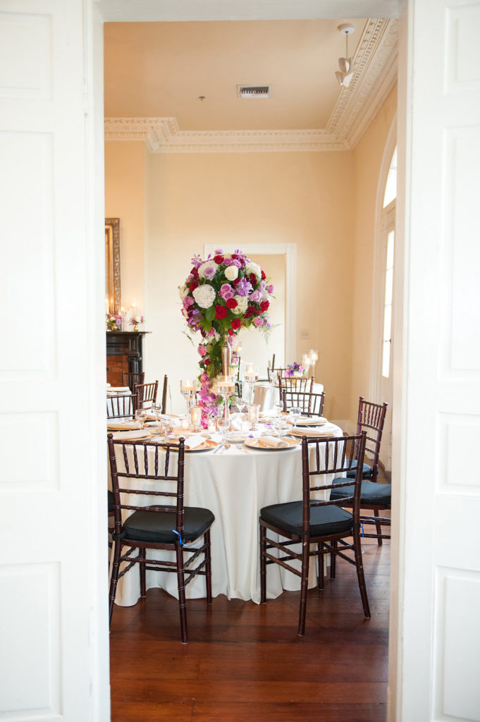 tall purple and pink floral arrangement with mahogany chiavari charis surrounding a dinner table inside a mansion in the french quarter