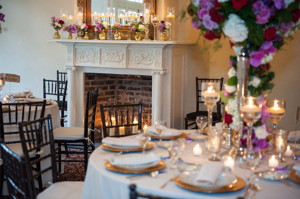 dinner tables set near a fireplace with candle light and pink and white flowers on tall gold vases