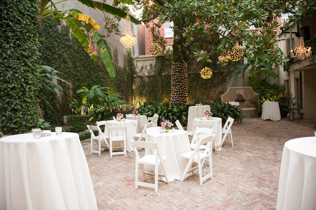 white chairs and white table cloths in a courtyard with green vines on the walls at an old live oak tree