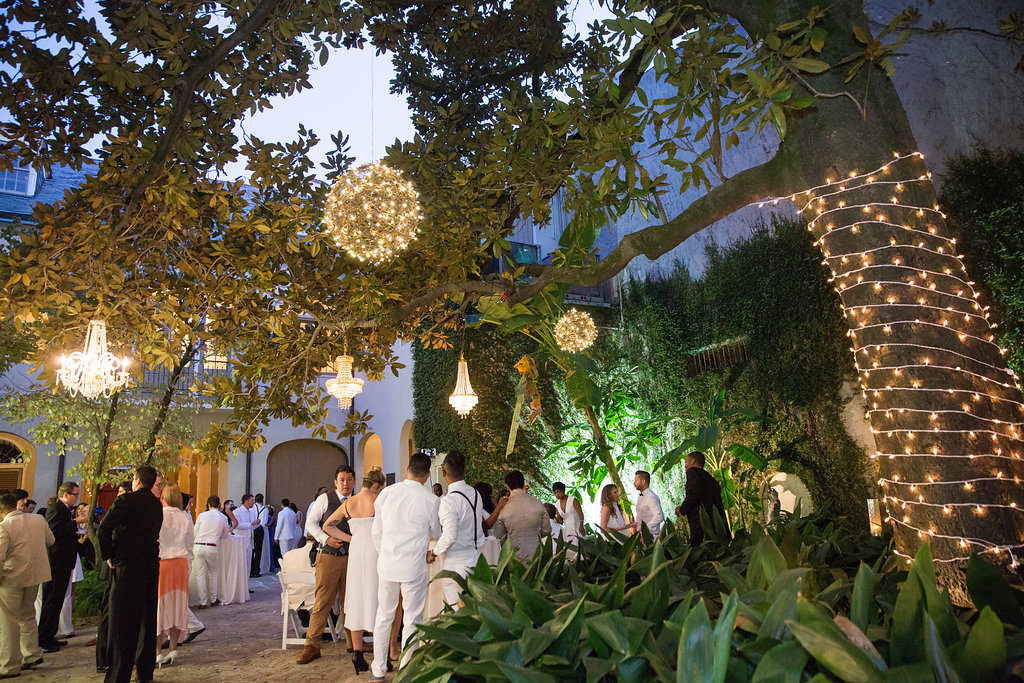 wedding guests dressed in white outside in a courtyard under chandeliers hanging in trees