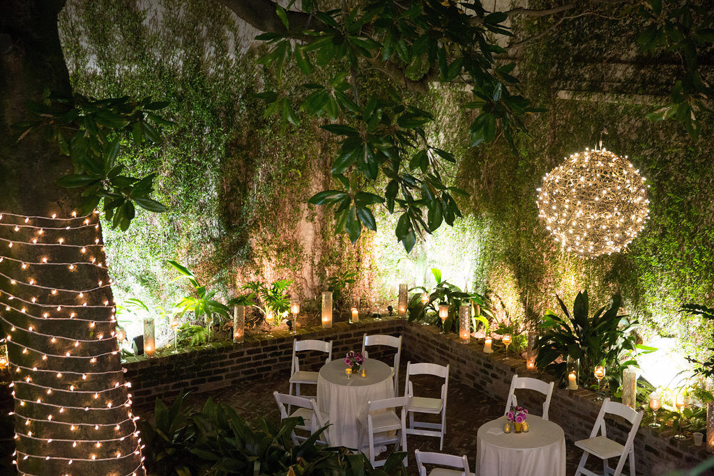 courtyard at night with grapevine chandeliers suspended from trees lit up in a verdant garden at wedding reception