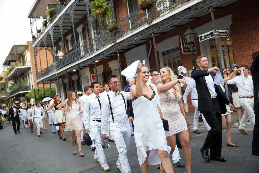 walking parade of wedding guests dressed in all white through New Orleans French Quarter during second line parade