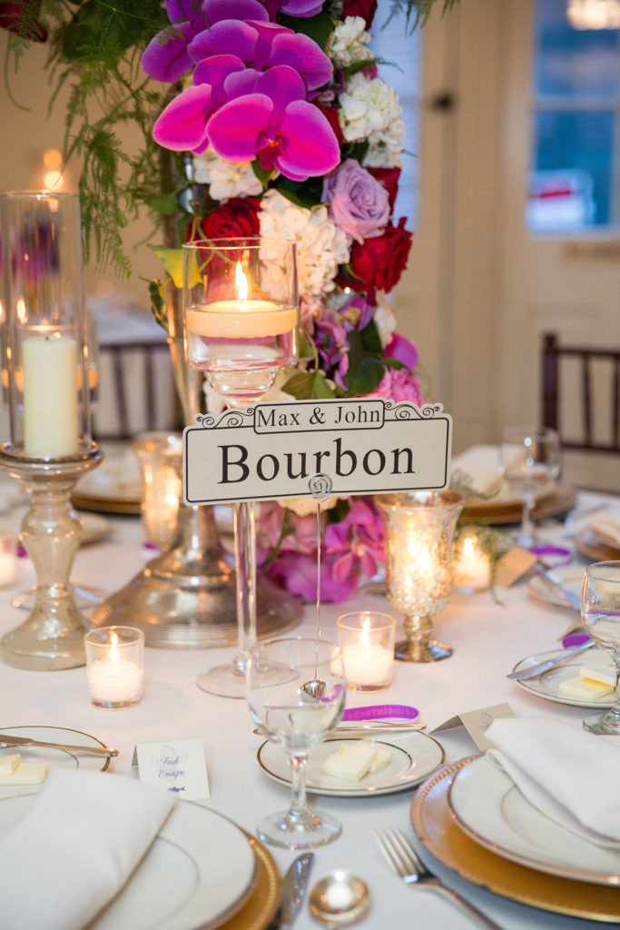 closeup of Bourbon street sign on a dinner table with candles and purple orchid floral arrangements
