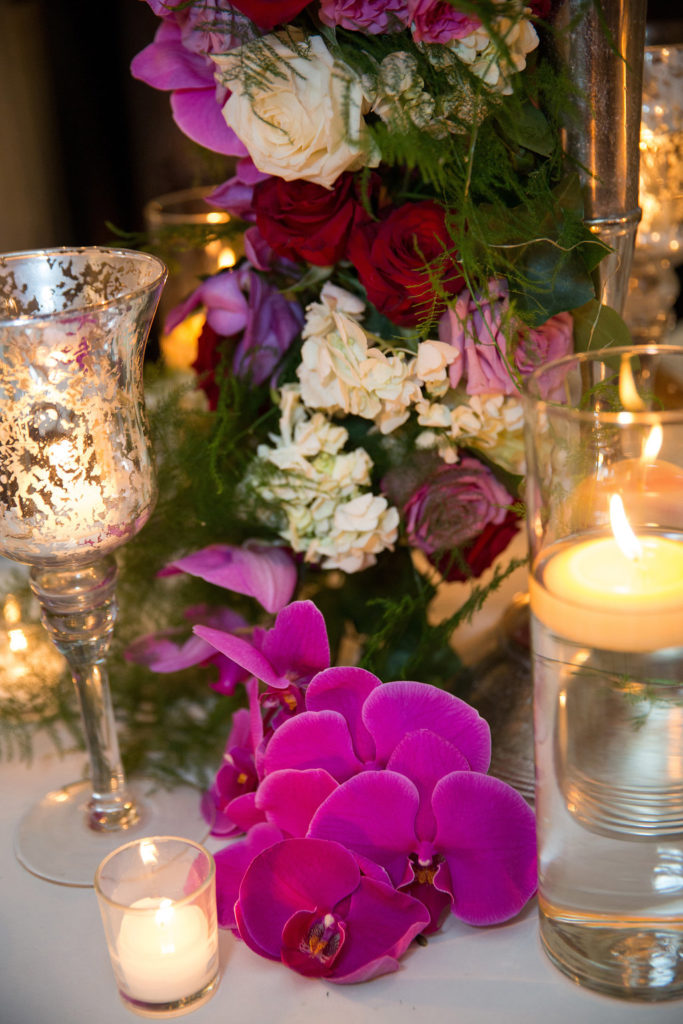 antique candles on a dinner table with purple orchid flowers at a wedding reception
