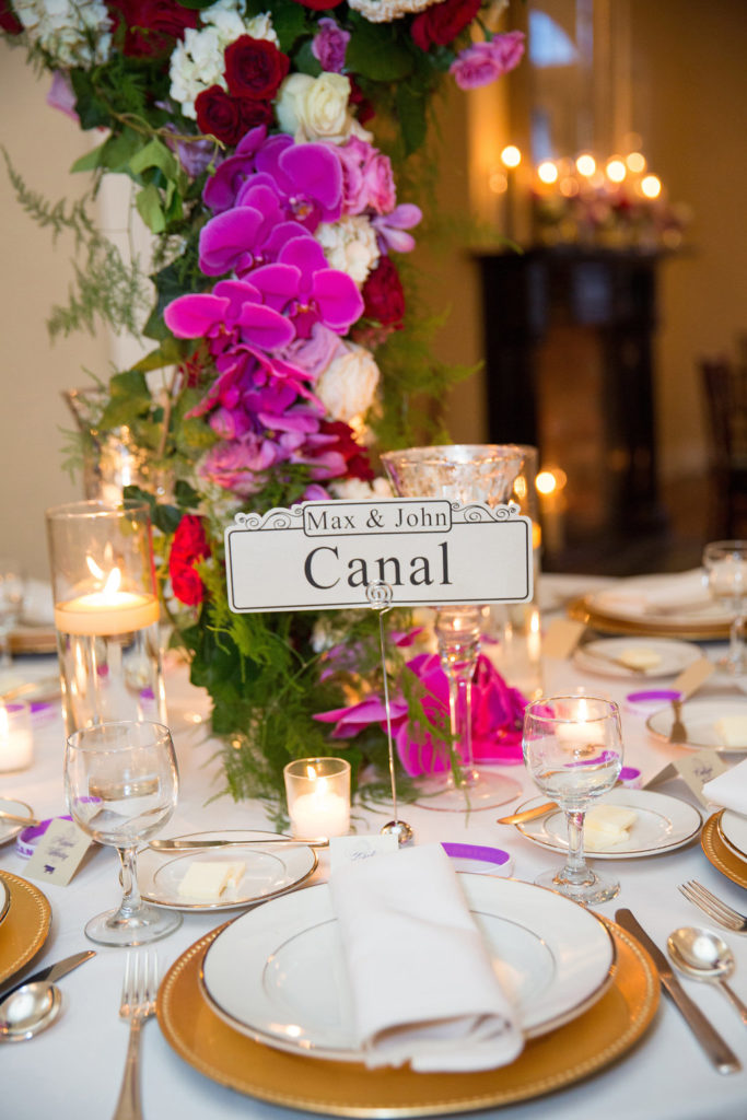 closeup of Canal Street sign at a dinner table with pink and purple orchid flowers