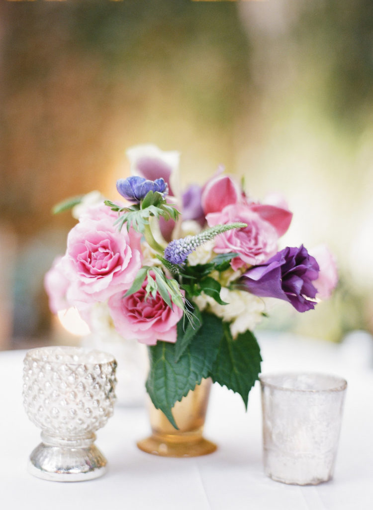 pink and purple floral arrangement in a gold julep cup on a white tablecloth